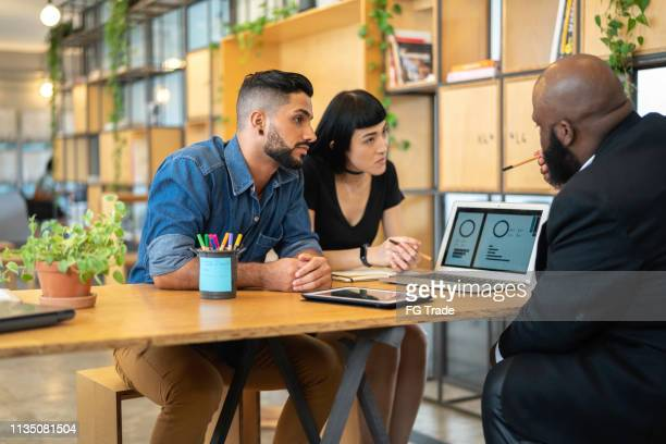 agent talking to a couple in the office - mortgage stock pictures, royalty-free photos & images