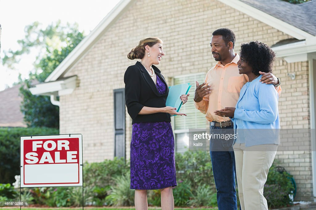 Agent talking with couple in front of house for sale : Stock Photo