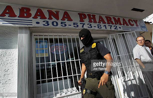 A agent walks out of the Cabana Pharmacy after raiding it along with the City of Miami Police Department's Crime Suppression Unit and Florida...