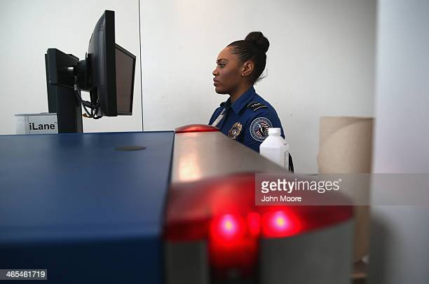 TSA agent watches xray monitors while screening luggage at a special TSA Precheck lane at Terminal C of the LaGuardia Airport on January 27 2014 in...