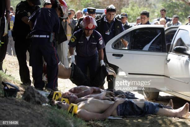 Agentes del Ministerio Publico y miembros del Cuerpo de Bomberos Muncipales retiran de un vehiculo de turismo los cadaveres de cuatro hombres...