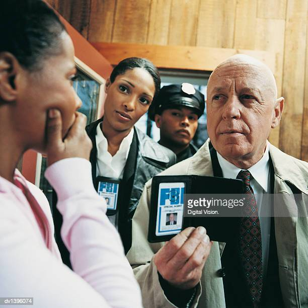 fbi agents approaching a woman in her home - fbi id stock pictures, royalty-free photos & images