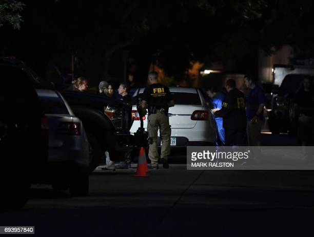 FBI agents assemble outside a house where federal investigators and local police held a raid and detained three people in the midcity area of Los...
