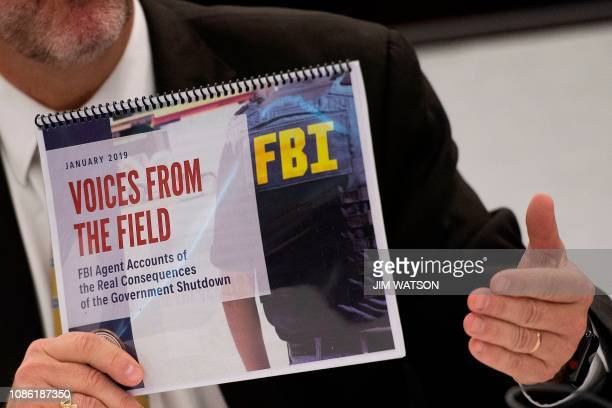 FBI Agents Association member Thomas O'Connor holds up an FBI report Voices From the Field giving examples of how the government shutdown is...
