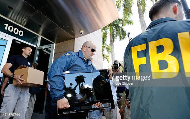 FBI agents carry boxes and computers from the headquarters of CONCACAF after it was raided on May 27 2015 in Miami Beach Florida The raid is part of...