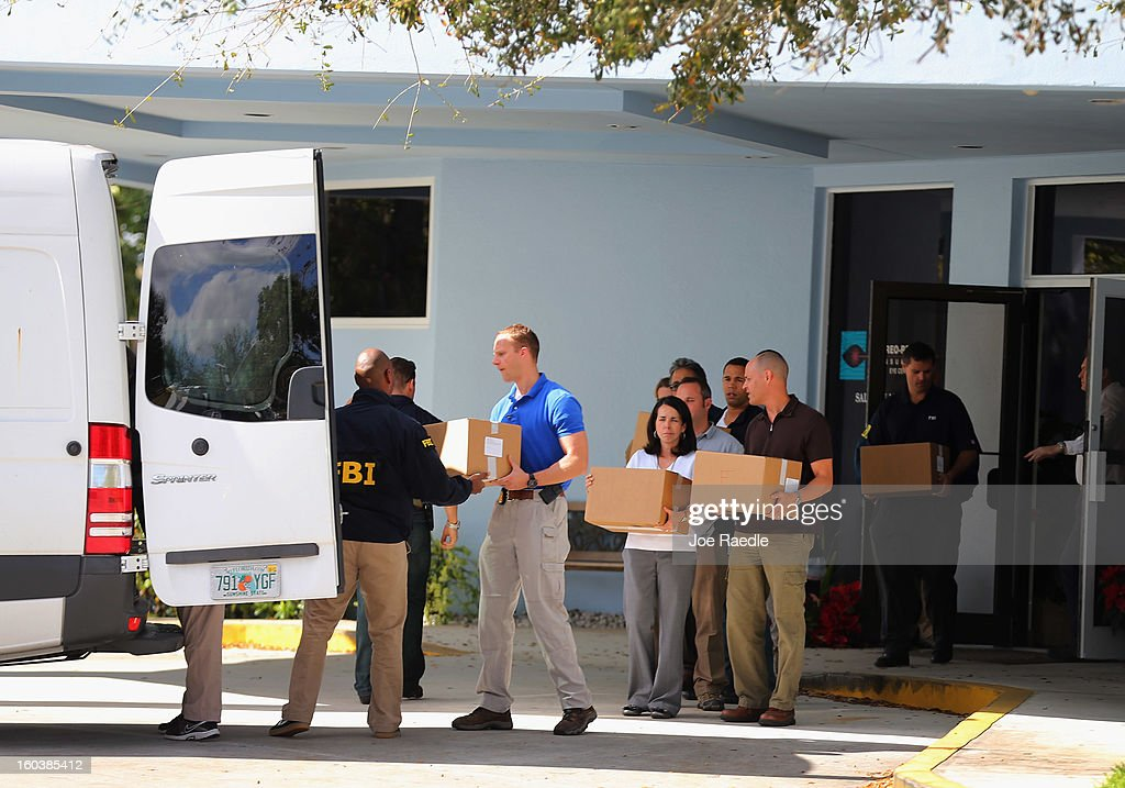 FBI agents carry out boxes as law enforcement officials investigate the medical-office complex of Dr. Salomon Melgen who has possible ties to U.S. Sen. Bob Menendez (D-NJ) on January 30, 2013 in West Palm Beach, Florida. The agents arrived last night at the medical-office complex and started hauling away potential evidence in several vans.