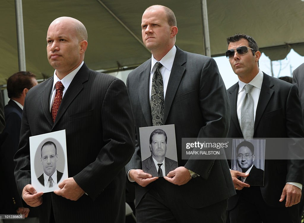 FBI agents carry photos of their deceased colleagues, during a memorial service for Special Agents and their law enforcement and military colleagues killed in the line of duty, at the Federal Building in Los Angeles on May 28, 2010. Memorial Day, which was formerly known as Decoration Day, commemorates US men and women who died while in the service to their country and was first enacted to honor Union soldiers of the American Civil War. AFP PHOTO/Mark RALSTON