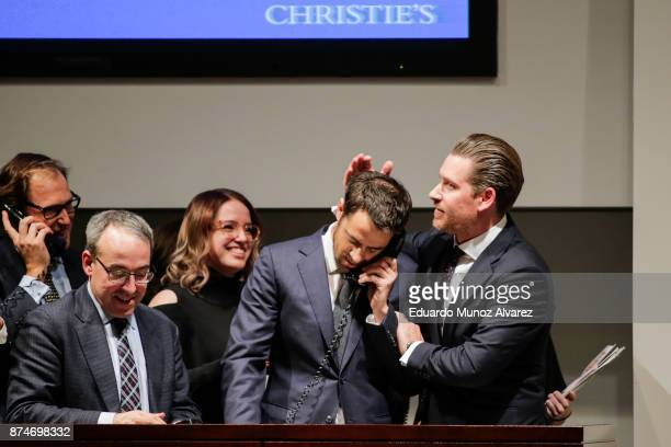 Agents celebrate after buying the auction of Leonardo da Vinci's Salvator Mundi during the PostWar and Contemporary Art evening sale at Christie's on...