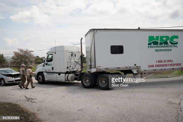 FBI agents check an environment services vehicle at the gate of the Arkema plant which received major damage from flooding caused by Hurricane and...