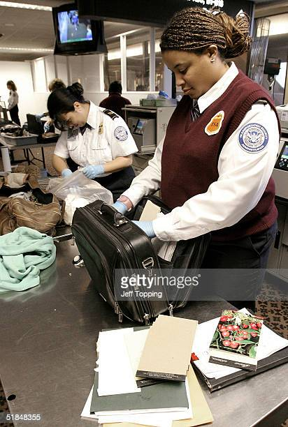 TSA agents check passengers carry on luggage at a security checkpoint in terminal four at Phoenix Sky Harbor International Airport December 10 2004...