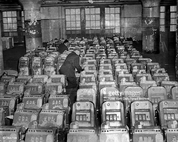 FBI agents check serial numbers on some of the 420 slot machines at Brooklyn Army Base after they were seized on a Brooklyn street