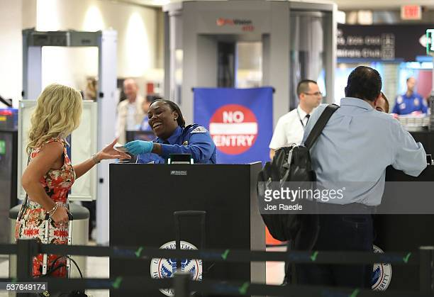 TSA agents check the documents of travelers as they go through the TSA PreCheck security point at Miami International Airport on June 2 2016 in Miami...