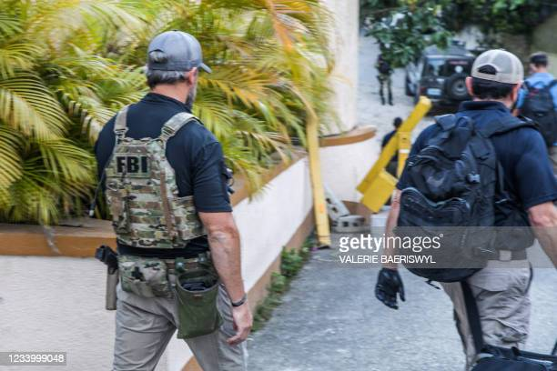Agents exit the residence of late Haitian President Jovenel Moise after conducting searches in Port-au-Prince on July 15 in the wake of his...