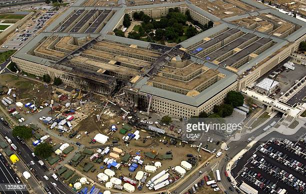 Agents, fire fighters, rescue workers and engineers work at the Pentagon crash site September 14, 2001 where a hijacked American Airlines flight...