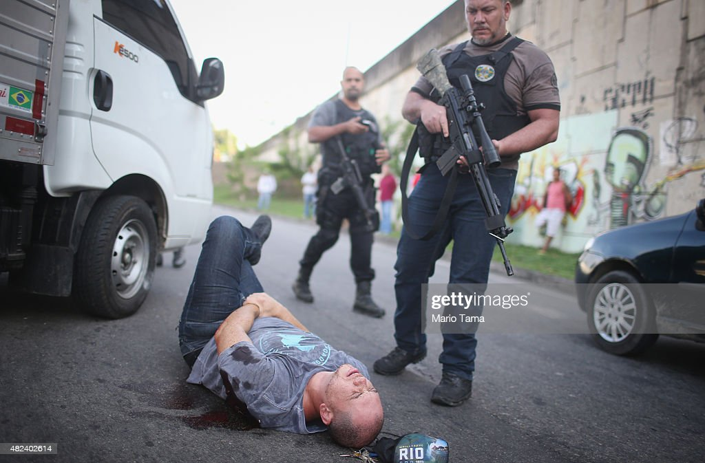 Agents from the Civil Police's Bureau of Robberies and Cargo Thefts surround a robbery suspect July 30, 2015 in Rio de Janeiro, Brazil. The suspect was shot by police during a shootout after police apprehended him driving an allegedly stolen vehicle during a patrol. Police said they found two illegal guns and radio transmitters in the vehicle and believe the suspect was planning to rob a cargo delivery. Officials are making efforts to improve security in the city ahead of the Rio 2016 Olympic Games. An increase in robberies along with a rash of recent stabbings and shootings has renewed concerns over security in the city ahead of the games which begin in just over one year.