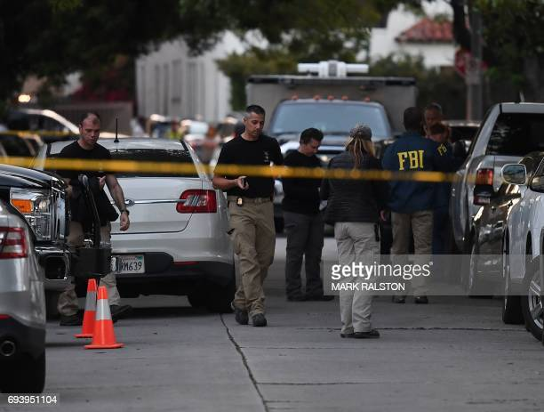 FBI agents gather outside a house where federal investigators and local police held a raid and detained three people in the midcity area of Los...