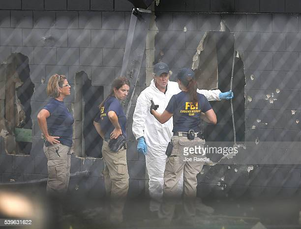 Agents investigate near the damaged rear wall of the Pulse Nightclub where Omar Mateen allegedly killed at least 50 people on June 12, 2016 in...