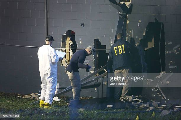 FBI agents investigate near the damaged rear wall of the Pulse Nightclub where Omar Mateen allegedly killed at least 50 people on June 12 2016 in...