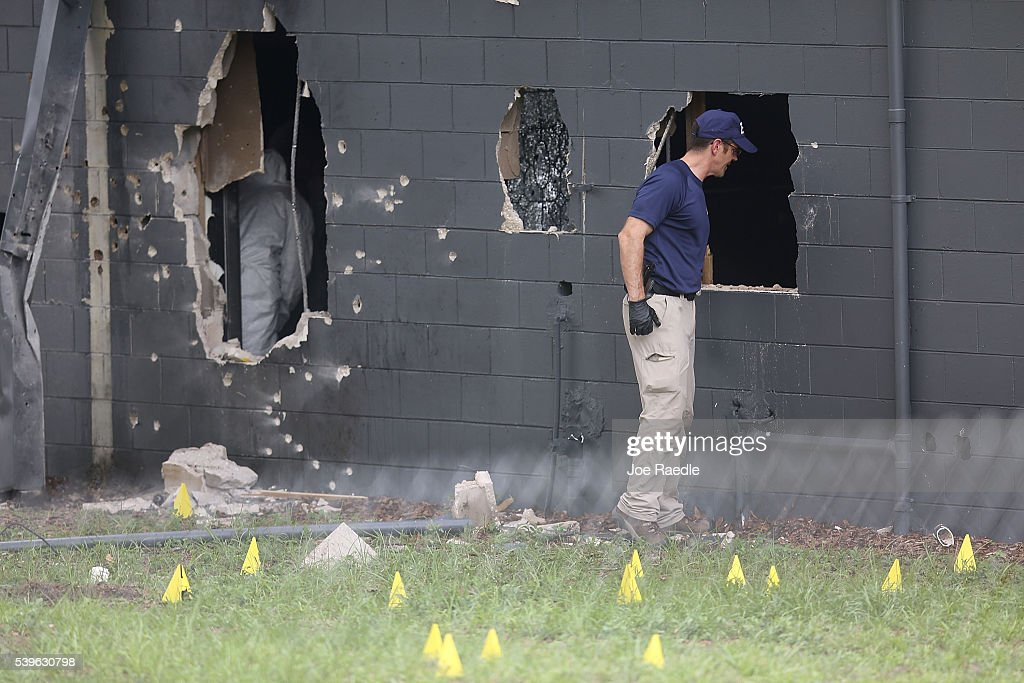 FBI agents investigate the damaged rear wall of the Pulse Nightclub where Omar Mateen allegedly killed at least 50 people on June 12, 2016 in Orlando, Florida. The mass shooting killed at least 50 people and injured 53 others in what is the deadliest mass shooting in the country's history.