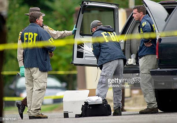 Agents load supplies into a truck 20 October 2002 in front of the Ponderosa Steak House where a 37 year old man was shot late 19 October in Ashland,...
