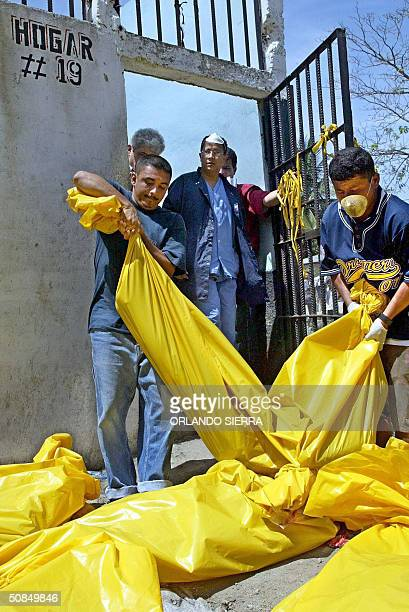 Agents of the General Direction of Investigation and prisoners carry in plastic bags the bodies of 103 inmates killed when a fire raged through a...