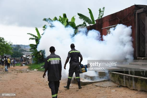 Agents of the National Institute of Public Hygene carry out fumigation in the Anyama district of Abidjan on June 9 as part of the ongoing fight...