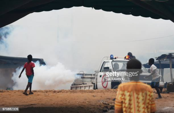 Agents of the National Institute of Public Hygene drive with a car as they carry out fumigation in the Anyama district of Abidjan on June 9 as part...