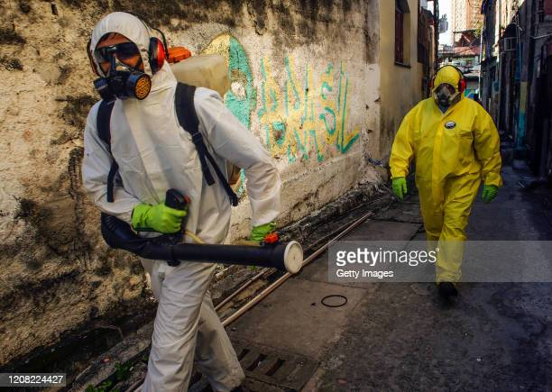 Agents of the sanitary department clean streets and alleys of the Vila Ipiranga Favela, in Fonseca neighborhood on March 25, 2020 in Niteroi, Brazil....