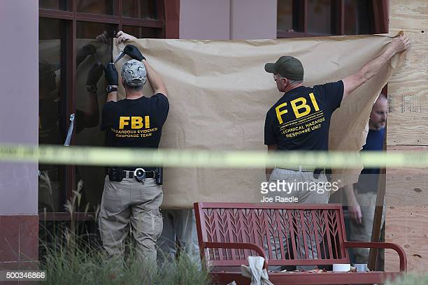 FBI agents put up a screen to block the view of onlookers as they investigate the building at the Inland Regional Center were 14 people were killed...