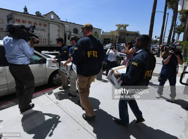 FBI agents remove boxes of documents from the offices of the California Investment Immigration Fund after serving search warrants in an investigation...
