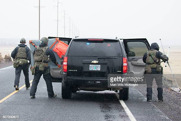 FBI agents removed a road block sign as a large group of law enforcement officials entered a checkpoint on the Malheur National Wildlife Refuge...