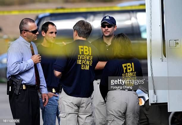 FBI agents talk outside the scene of a raid of the apartment of Najibullah Zazi at the Vistas Apartment Complex at 22959 East Smoky Hill Road in...