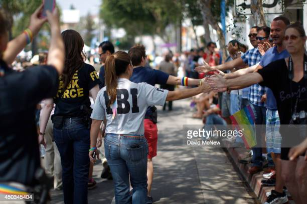 FBI agents touch hands with spectators as they march in the LA Pride Parade on June 8 2014 in West Hollywood California The LA Pride Parade and...