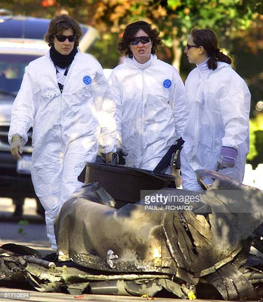 Agents walk near engine cowling 14 November 2001 from the jet engine that fell off American Airlines Flight 587, an Airbus A 300 jet that crashed 12...