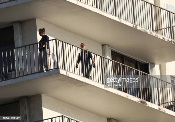 Agents walk on along the balcony of a condo in the building that has a possible connection to alleged bomber Cesar Sayoc and his mother on October 26...