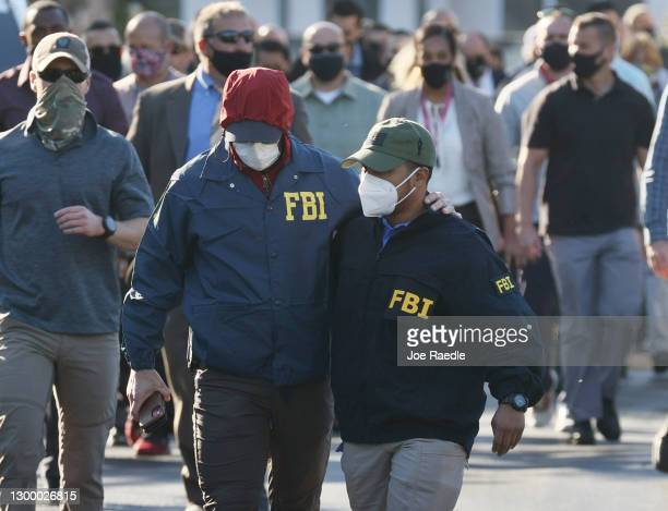 Agents walk together as they leave the Broward County Office of Medical Examiner and Trauma Services after the killing of two FBI agents during the...