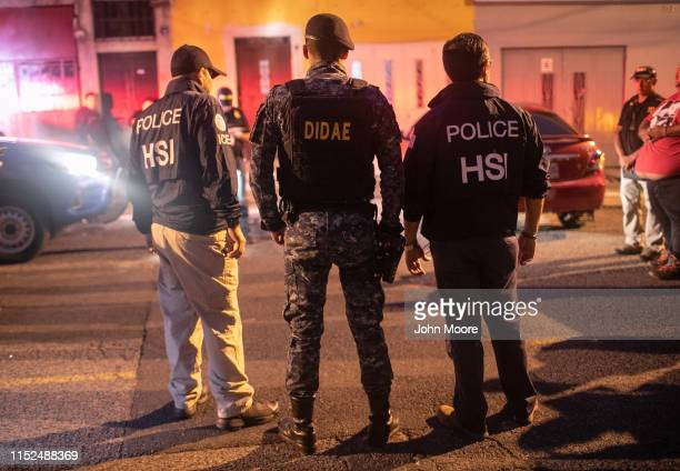 ICE agents with US Homeland Security Investigations and a Guatemalan policeman stand at the scene of an early morning raid where a suspected human...