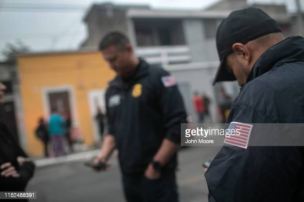 ICE agents with US Homeland Security Investigations stand at the scene of an early morning raid where a suspected human trafficker was taken into...