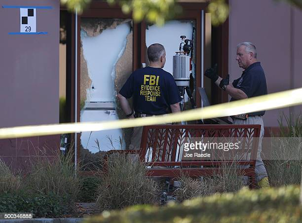 FBI agents work next to broken out glass doors as they investigate the scene in the building at the Inland Regional Center were 14 people were killed...
