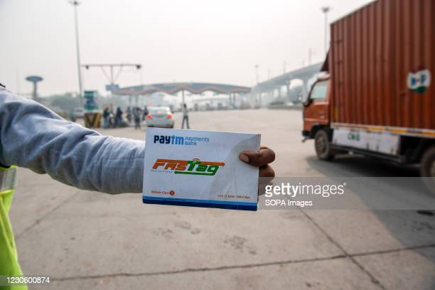 Agent/salesman of 'Paytm Payments Bank' selling Fastag showing a Fastag pass at Sarai toll plaza Faridabad. In India fastag system will become...