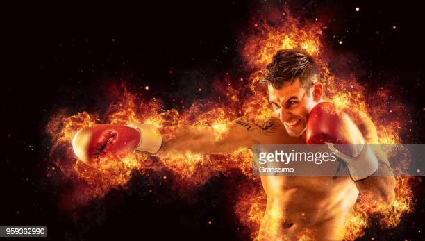 Aggressive athlete boxing with gloves surrounded by fire and flames
