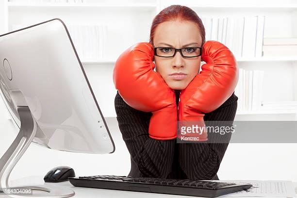 Aggressive Geschäftsfrau mit Boxhandschuhen in Ihrem Büro