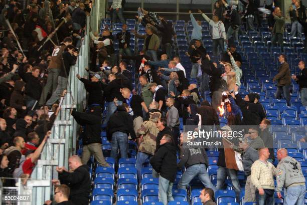Aggressive fans of Rostock fight and throw objects at St. Pauli fans after the Second Bundesliga match between FC Hansa Rostock and FC St. Pauli at...