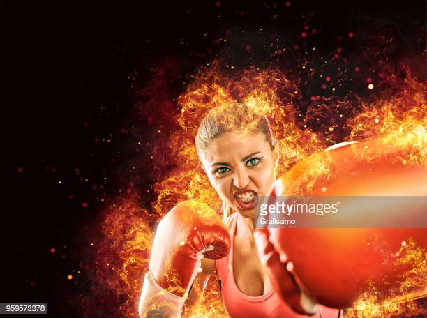 Aggressive female athlete boxing with gloves surrounded by fire and flames
