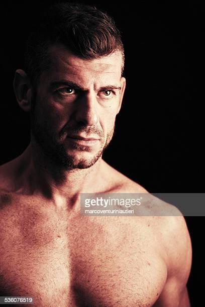 aggressive muscular macho man in the dark - a dark foe stockfoto's en -beelden
