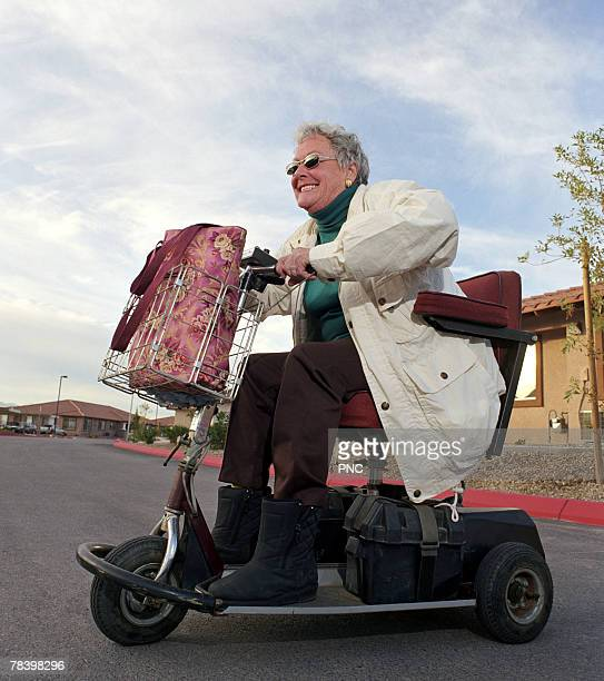 aggressive senior woman in motorized scooter - mobility scooter stock photos and pictures