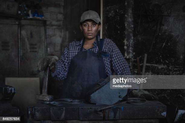 Aggressive woman in iron workshop