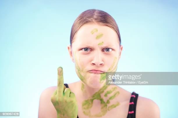 aggressive woman showing middle finger against blue background - kid middle finger stock pictures, royalty-free photos & images