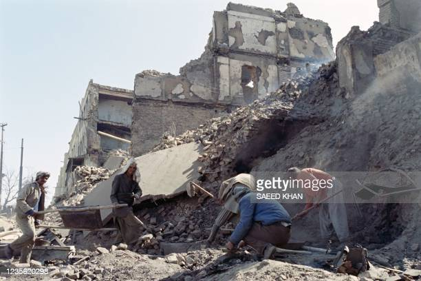 Aghan men remove stones of a house destructed by rockets, on February 21, 1993 during a temporary cease fire among rival factions.