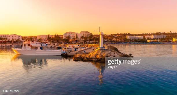 opinião do porto de agia napa no por do sol com barcos de pesca foto de stock - república do chipre - fotografias e filmes do acervo